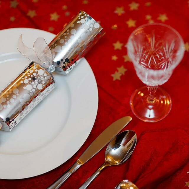 a festive holiday place setting with crystal goblet and red tablecloth