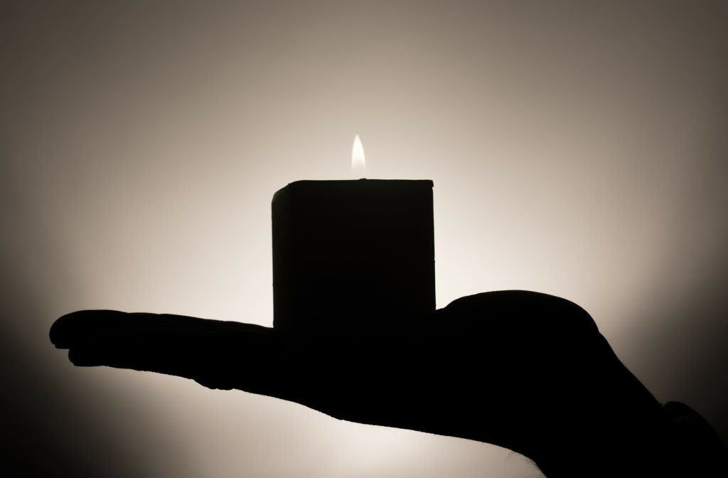 The silhouette of a hand holding a lit candle