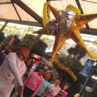 A Piñata with children surrounding it during a celebration of Las Posadas