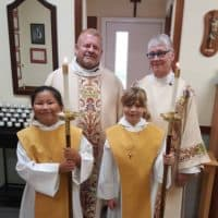 An altar party of priest, deacon, and two acolytes prepares to process for a service