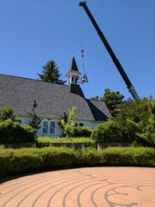 A crane lifting the refurbished bell into the bell tower of Trinity Church, Ashland