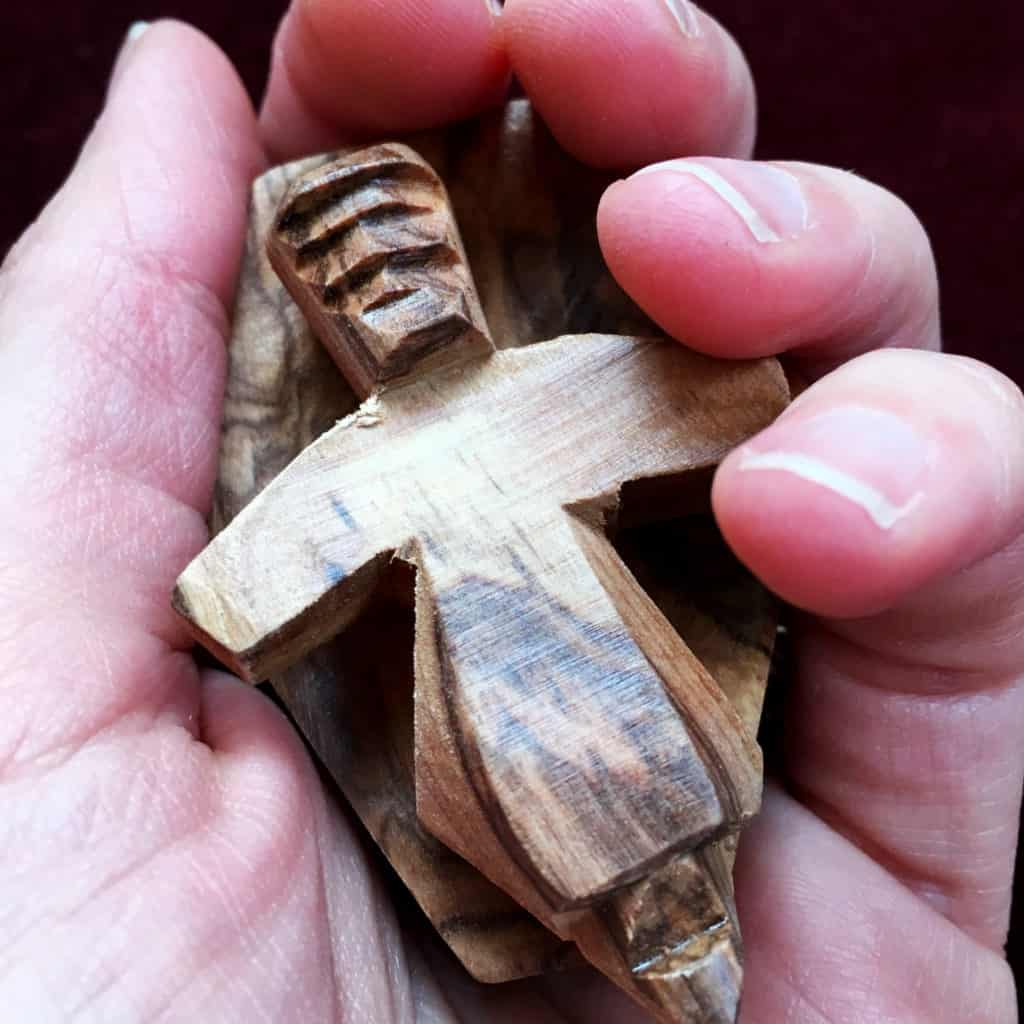 a wooden figure of the infant Jesus held cradled in a human hand