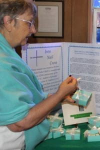 A woman with short gray hair, glasses, and a turqoise scarf unties a white ribbon from a small turqoise box in front of a table covered with small turqoise boxes