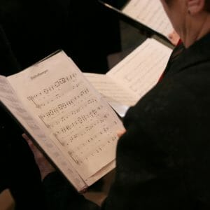 a person in black looks at choir sheet music in a folder