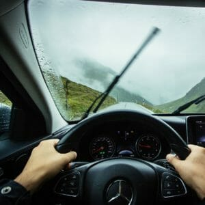 two hands grip a black steering wheel, a windshield with raindrops and windshield wipers moving