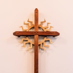 a simmple cross made of medium brown wood with a sunflare design in lighter brown surrounding the center of the cross