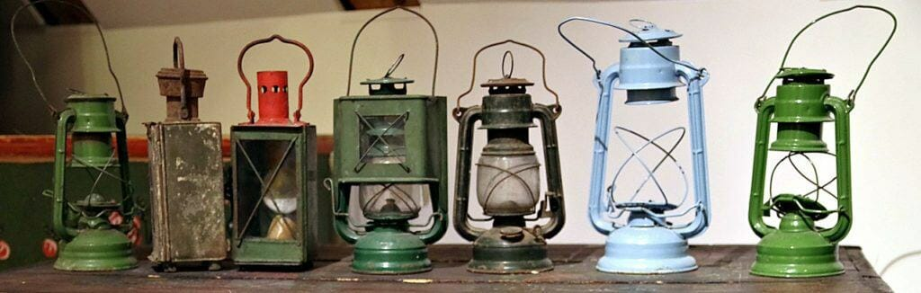 seven old kerosene lanterns in shades of green, blue, and brown on a wooden shelf