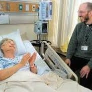 a hospital chaplain sits next to a hospital bed with a smiling woman