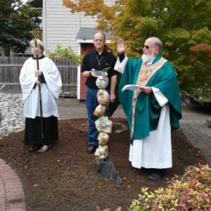 A male priest with a long white beard wearing a green robe raises his hand above a statue of shells next to the edge of a brick labyrinth. In the background, a woman with short blond hair holds a tall stick with a cross on top.