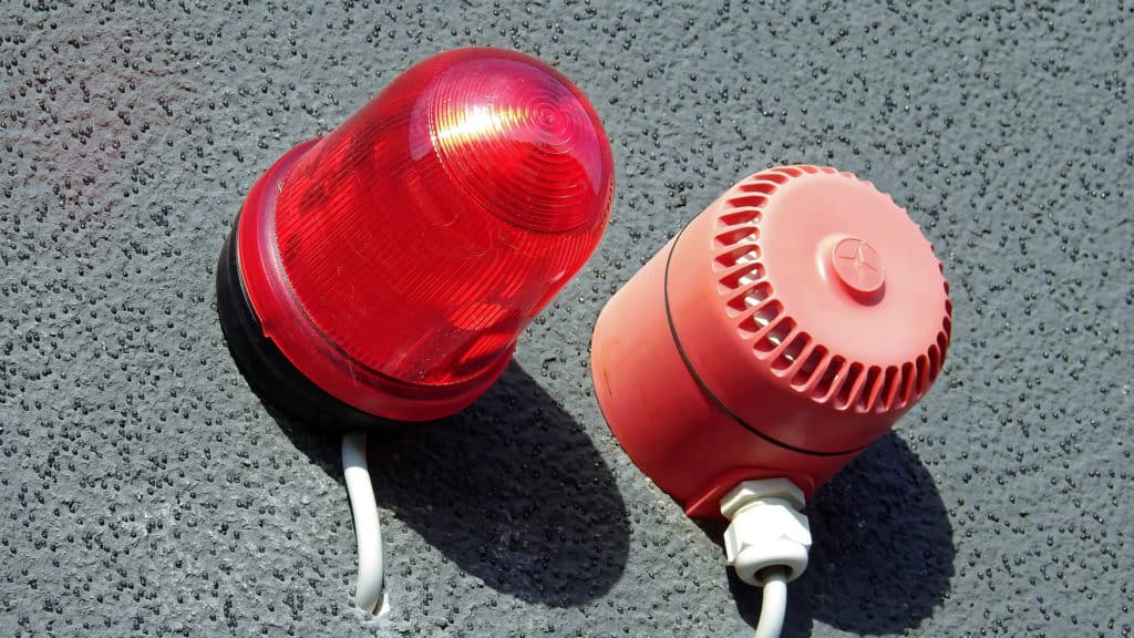 a red warning light is set into a grey wall next to a red speaker for warning sirens