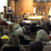 in the background is the warm wood altar with many lit white candles. a woman stands at the lectern reading. in the foreground many people sit in pews