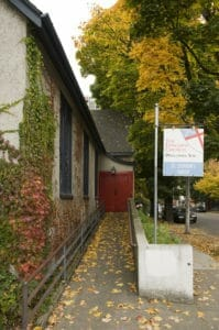 """wheelchair ramp from sidewalk to the red doors of St. Stephen's Episcopal Church, Portland with the classic """"The Episcopal Church Welcomes You"""" sign next to the sidewalk"""