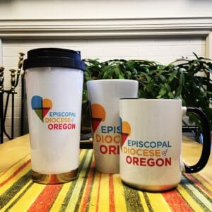 three mugs of various sizes featuring the new diocesan logo standing on a striped table runner