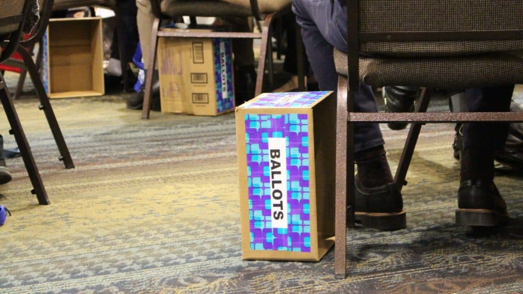 A ballot box used by Convention Delegates to submit their votes rests on the floor next to a chair and feet in black shoes and socks.
