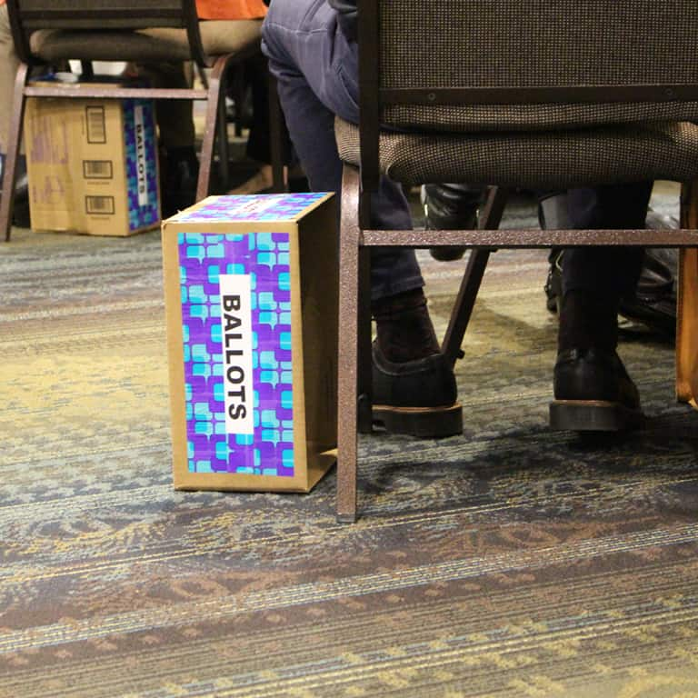 a ballot box for collecting votes from convention delegates sites on the floor next to a chair and a set of feet in black shoes and socks