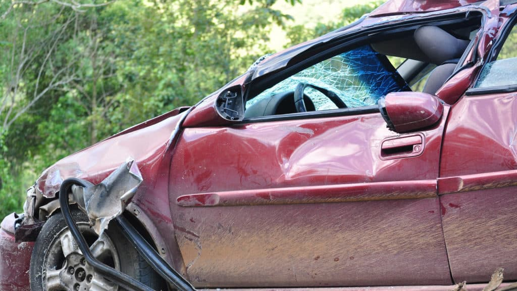 the front of a maroon colored car which is smashed up due to a disaster