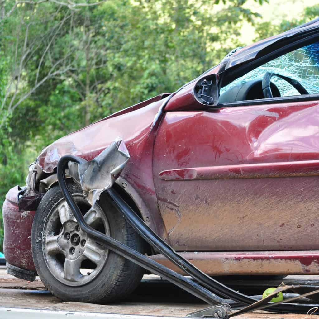 the front end of a maroon car that has been crashed in a disaster