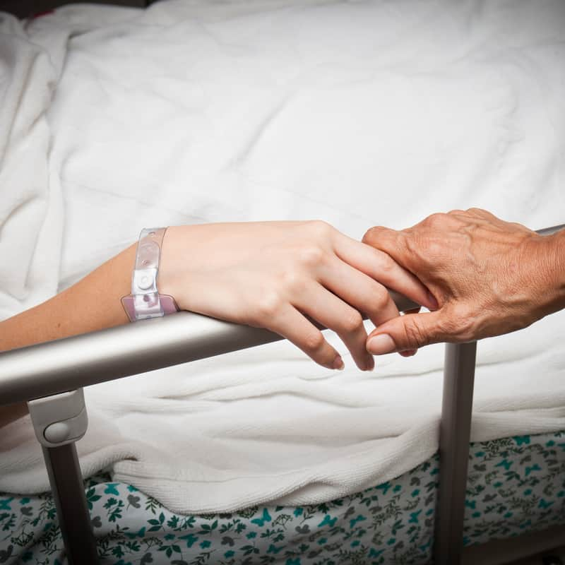 hands holding on the bar of a hospital bed