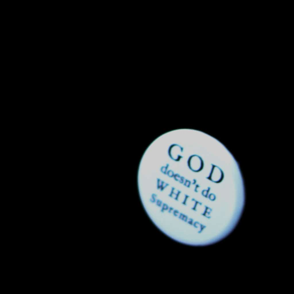 """white button with text """"God doesn't do white supremacy"""" on a black background"""