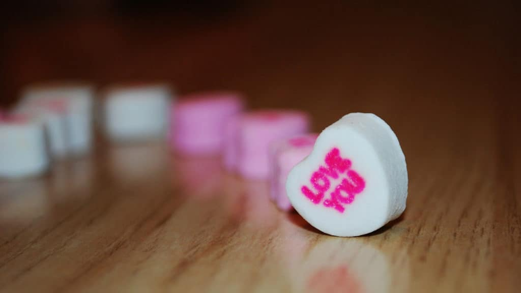 "A white Valentine's Day candy heart with the words ""Love You"" in pink letters"